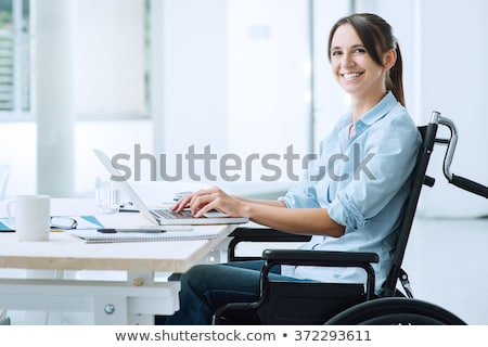 Worker in wheelchair working on computer smiles to camera Stock photo © wavebreak_media