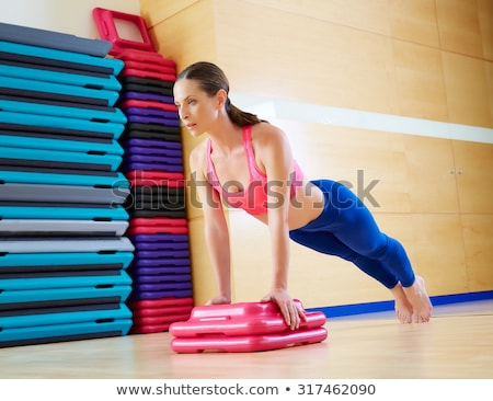 Concentrated beautiful fitness girl in sportwear exercising with pink fitball  Stock photo © deandrobot