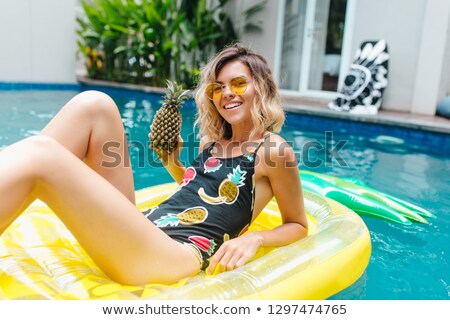 young pretty woman lying on yellow air mattress in the pool stock photo © dashapetrenko
