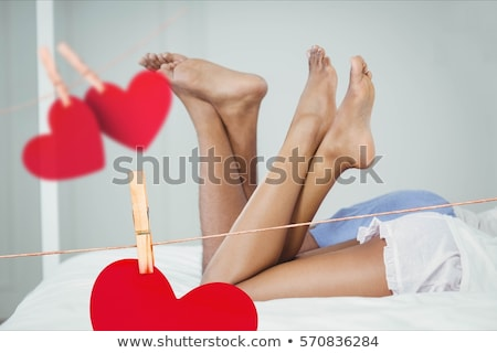 composite image of red hanging hearts and couple lying on bed stock photo © wavebreak_media