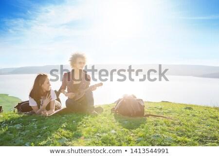 Pretty young woman sitting on mountain top and contemplating lan Stock photo © Yatsenko