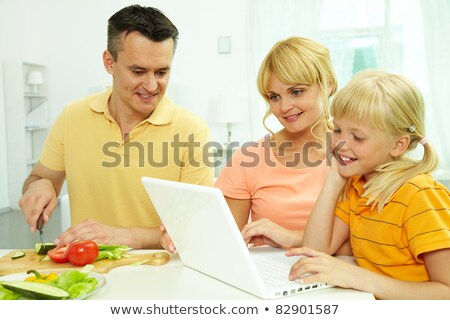 Сток-фото: Man Using His Laptop While Daughter Preparing Food