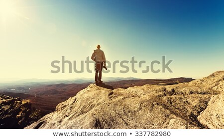 man standing on rocks looking at peaks stock photo © is2