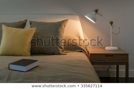 Stock photo: Book and vintage lamp on night table in hotel room