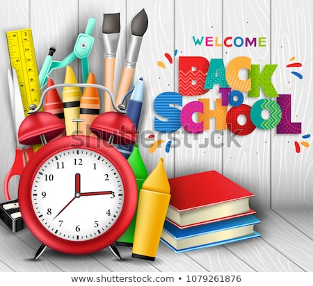 books with alarm clock with books and paintbrushes on wooden table against shelf of books stock photo © wavebreak_media