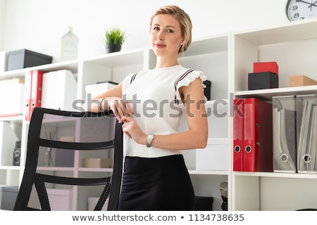 A young girl is standing in the office next to the shelving, talking on the phone and holding a fold Stock photo © Traimak