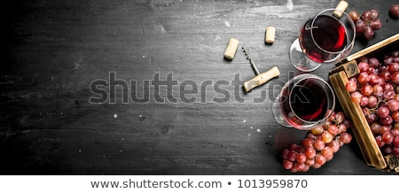 Glass of red wine with vintage corkscrew opener and cork on wooden board on black background.  Stock photo © DenisMArt