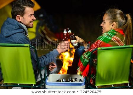 happy couple drinking beer at campsite tent Stock photo © dolgachov