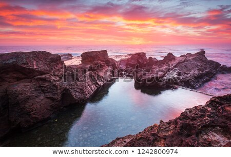 blazing red sunrise over rock pool stock photo © lovleah