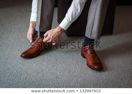 Young man tying elegant shoes indoors stock photo © ruslanshramko