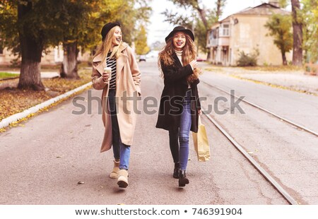 pretty young happy women friends walking outdoors with backpacks hugging pointing stock photo © deandrobot