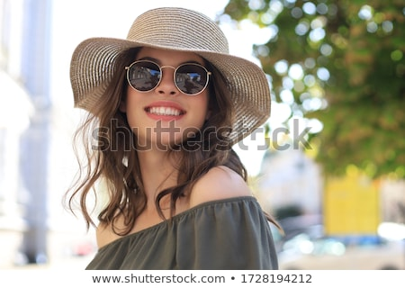 Beautiful brunette woman in sunglasses smiling at camera. stock photo © studiolucky