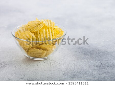 Homemade potato crisp chips inside glass bowl flavoured with dill on light board background. Stock photo © DenisMArt