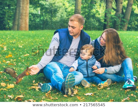 Dad and son feed a squirrel in the park Stock photo © galitskaya