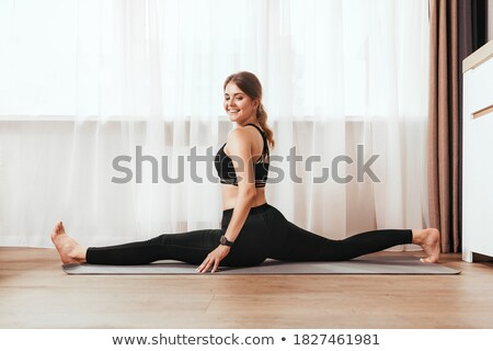 Delighted healthy woman with slim body, stretches legs for doing splits, raises hands, has workout i Stock photo © vkstudio