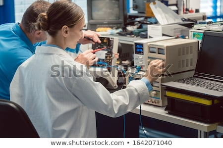 Engineer woman measuring electronic product on test bench Stock photo © Kzenon