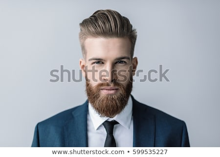 Image of handsome bearded businessman posing and looking forward Stock photo © deandrobot