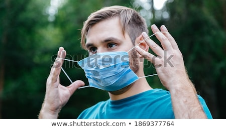 Man traveler wears protective disposable medical mask in airport, returns from abroad where coronavi Stock photo © vkstudio