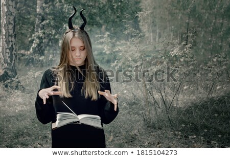 Beautiful girl against a dark background with book stock photo © pzaxe