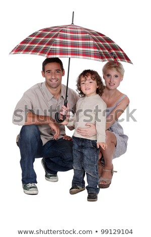 young family crouching under an umbrella stock photo © photography33