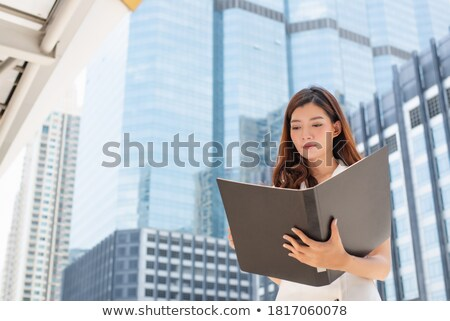 Cheerful secretary holding business files Stock photo © stockyimages