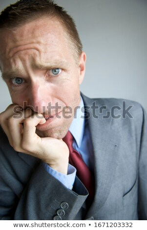 Businessman chewing on his fingernails with a worried expression Stock photo © Rugdal