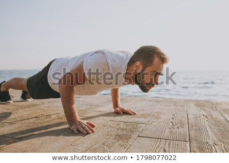 Portrait of a healthy young guy doing push ups Stock photo © pxhidalgo