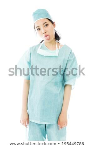 asian female surgeon poking out tongue towards camera isolated on colored background stock photo © bmonteny