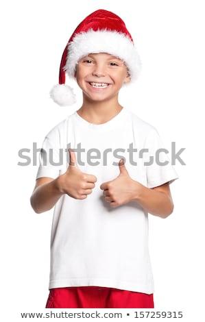 smiling happy boy in santa hat showing thumbs up stock photo © dolgachov