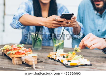 woman taking pictures of food with mobile phone in cafe stock photo © deandrobot