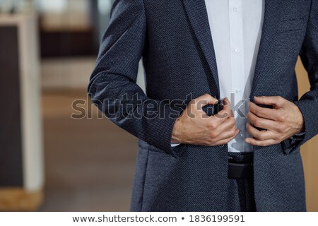 young businessman in tuxedo buttoning his coat Stock photo © feedough