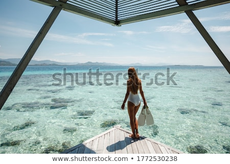 woman holding snorkelling equipment, standing in sea Stock photo © Kzenon