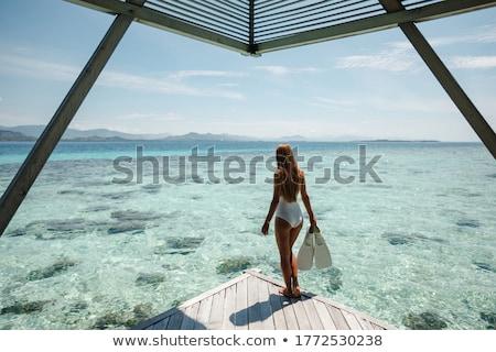 woman holding snorkelling equipment, standing in sea Stock photo © Kzenon