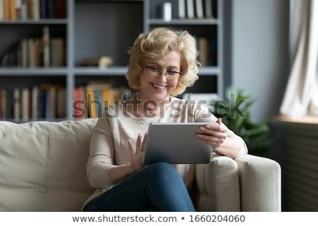 シニア · 女性 · ラップトップを使用して · イヤホン · リラックス · ソファ - ストックフォト © studiostoks