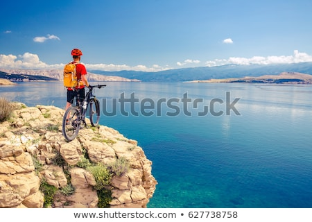 Mountain biker looking at view and riding on bike stock photo © blasbike