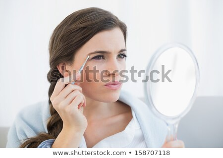 Female Plucking Her Eyebrow Hair With Tweezers Stock photo © AndreyPopov