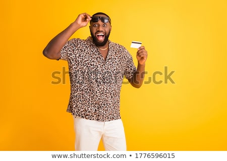 photo of handsome man in white shirt holding credit card and sma stock photo © deandrobot
