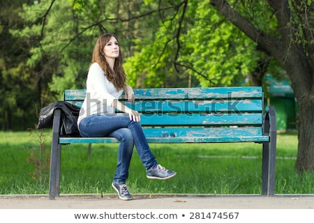 lovely young girl sitting on a bench at the park stock photo © deandrobot