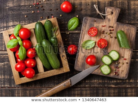 Organic Tomatoes and cucumbers with basil and linen towel in vintage wooden box on wooden kitchen ta stock photo © DenisMArt