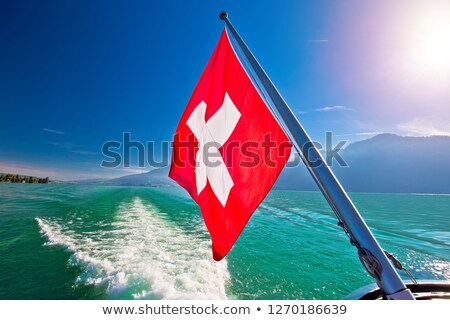 Flowing on idyllic Swiss lake Lucerne boat flag view Stock photo © xbrchx