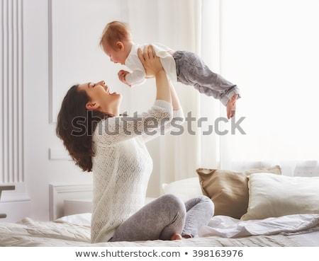 familia · cama · jugando · sonriendo · mujer · ninos - foto stock © lopolo