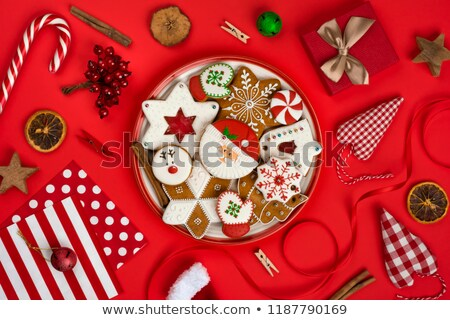 Christmas background, gingerbread cookies, candy canes and anise stars laying on red background. Mer Stock photo © ikopylov