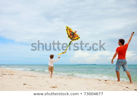 Young father and his son running with kite on the beach Stock photo © galitskaya