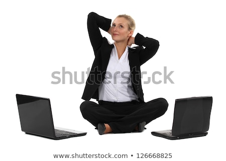Stock photo: Blond businesswoman sat cross-legged with two laptops