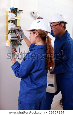 a young female electrician using an ammeter for checking an electricity meter and an older man watch Stock photo © photography33
