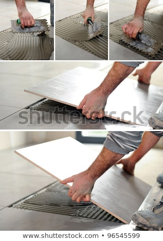 Stock photo: handyman spreading glue on the floor