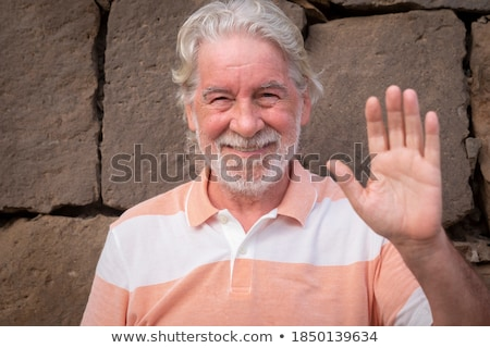 Smiling man standing in front of a stone wall Stock photo © photography33