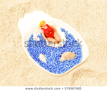 blond in blue bikini with shell on white sand stock photo © dolgachov