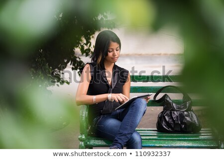 Stock photo: hispanic woman with digital tablet pc on bench