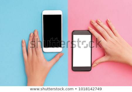two beautiful girls with phones isolated on white stock photo © acidgrey